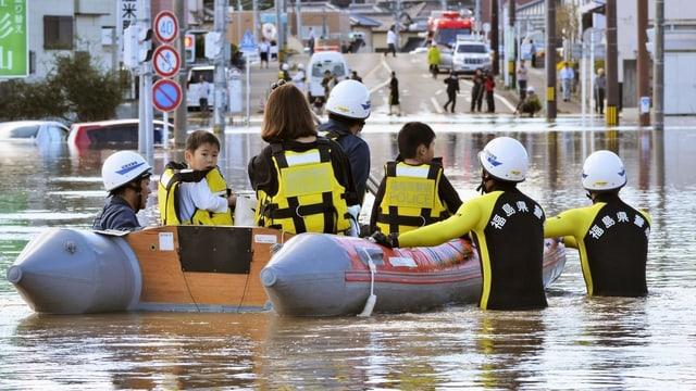 Menschen und Helfer auf und an einem Schlauchboot