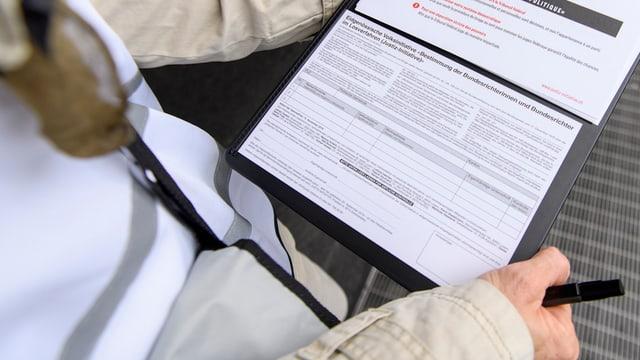 Ein Mann hat einen Unterschriftenbogen in der Hand.