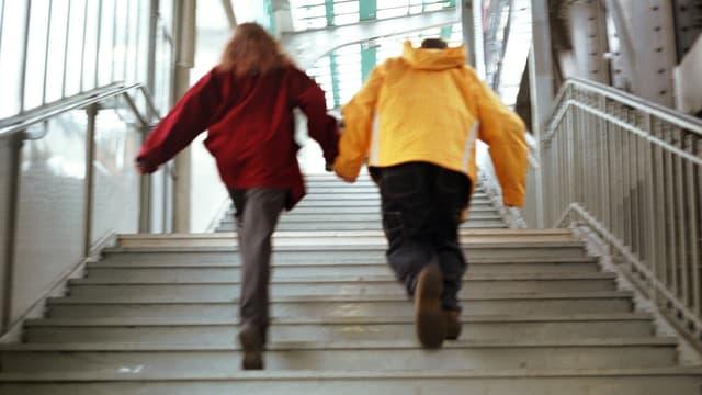 Zwei Personen rennen Hand in Hand eine Treppe hoch
