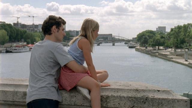 Junger Mann steht auf einer Brücke, ein Mädchen sitzt vor ihm auf dem Geländer, das eine Steinmauer gleicht.