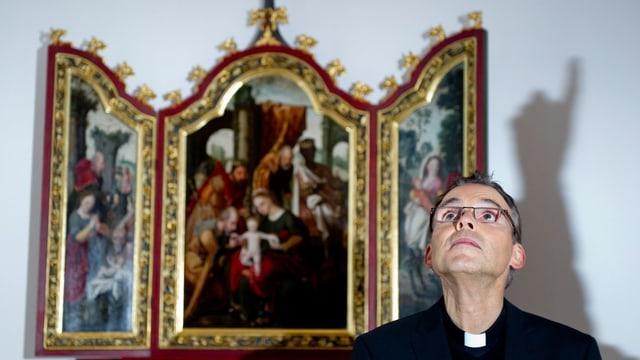 Archivbild mit Bischof Franz-Peter Tebartz-van Elst vor einem Flügelaltar und dem Schatten eines hochgestreckten Zeigefingers.