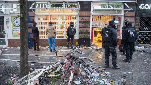 policists e glieud avant stizuns e velos demolids en ina via a Hamburg