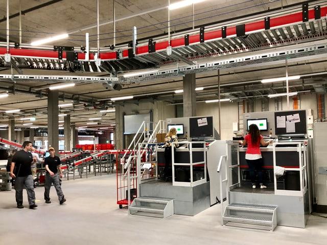 Fliessbänder und Mitarbeiterinnen und Mitarbeiter an Bildschirmen.