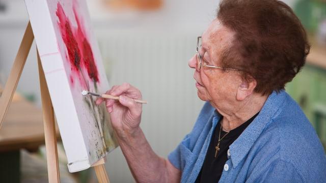 Eine ältere Frau sitzt an der Staffeli und malt Blumen auf die Leinwand.