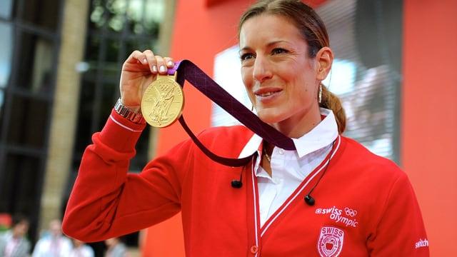 Nicola Spirig präsentiert ihre olympische Goldmedaille.