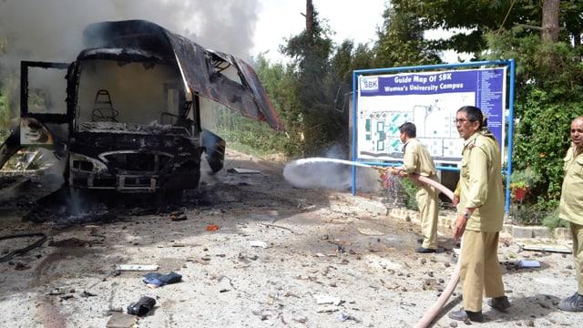 Feuerwehrmänner vor einem brennenden Bus