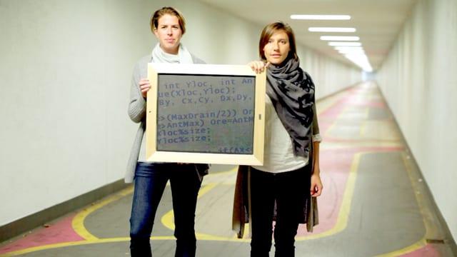 Maya Baas und Terry Harker halten in einem Gang ein Schild mit Code.