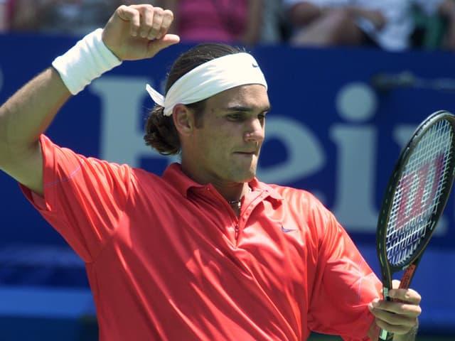 Federer schlägt mit der Faust in Richtung seines Rackets.