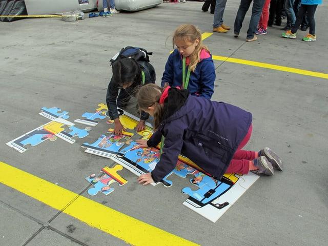 Drei Mädchen knien auf dem Boden und setzen ein Puzzle zusammen.