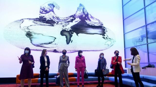 Sieben Frauen stehen vor einem Screen.