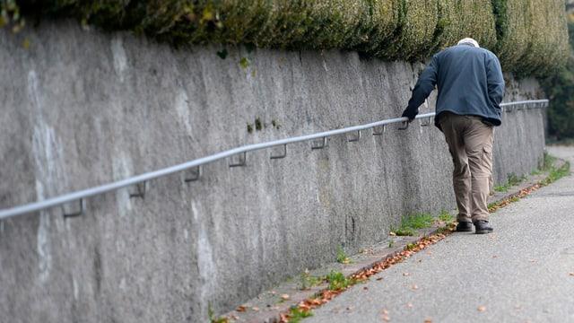 Ein älterer Mann läuft auf einem Gehsteig entlang eines Geländers.