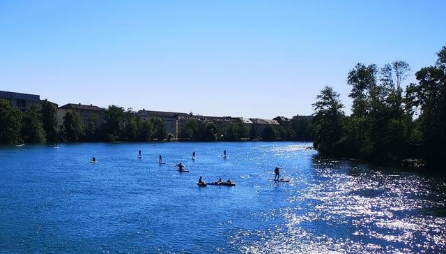 Breiter Fluss an einem Sommertag, darauf viele Paddler.