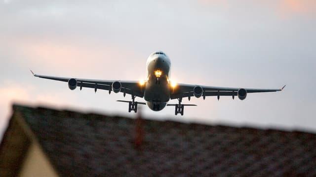 Flugzeug fliegt über Hausdach.