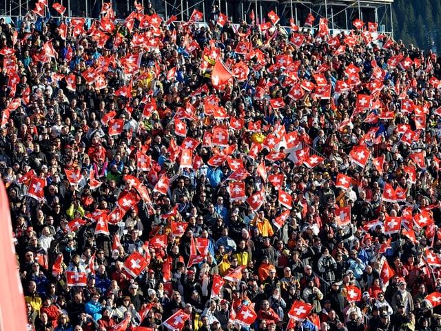 Menschenmenge am Skirennen in Adelboden. Viele schwingen eine Schweizer Fahne.