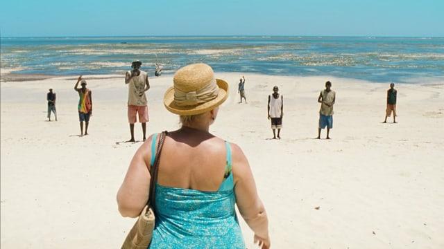 Die 50jährige Wienerin Teresa am Strand in Kenia mit einigen Einheimischen Männern.