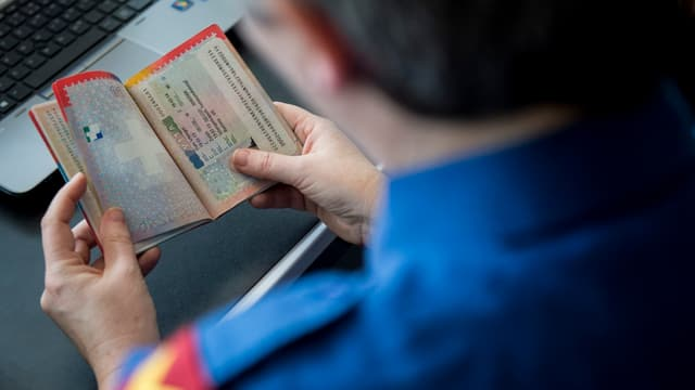 Polizist schaut Schweizer Pass an