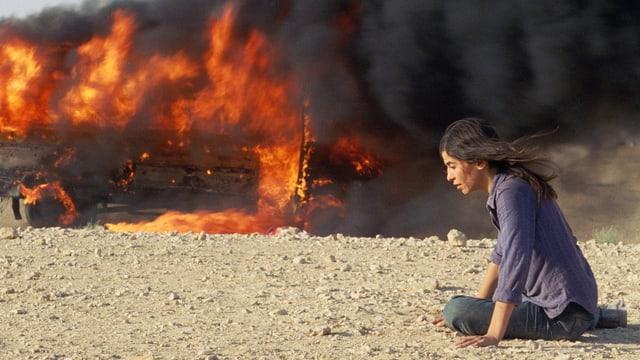 Eine Frau kniet erschöpft vor einem brennenden Bus.