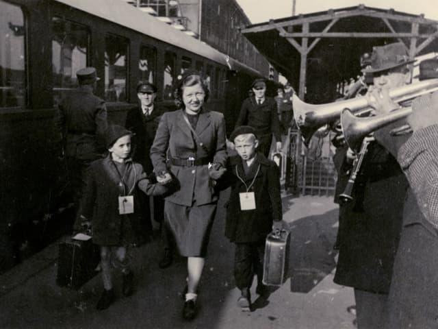 Eine Frau läuft auf dem Bahnsteig mit zwei Kinder links und rechts von ihr an der Hand.