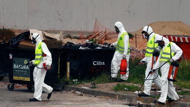 Arbeiter in Schutzanzügen sprühen Desinfektion in Strasse