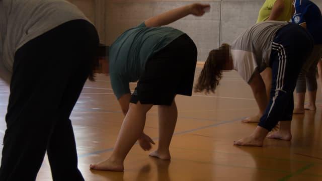 Die Teilnehmer machen Übungen in einer Turnhalle.