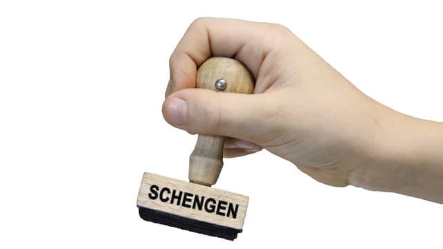 Eine Hand hält einen Stempel, der mit «Schengen» beschriftet ist.