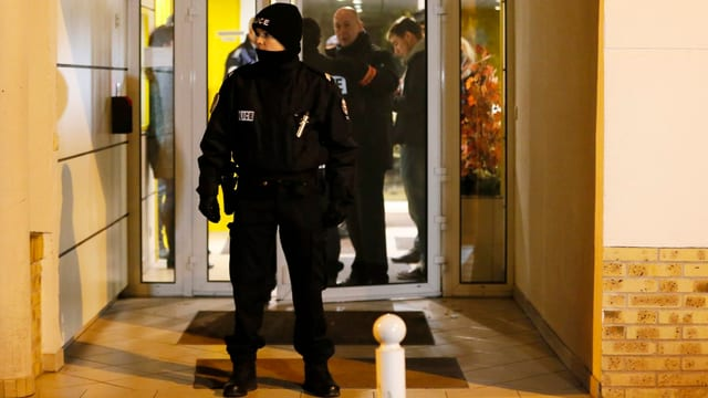 Ein Polizist steht vor einer Tür.