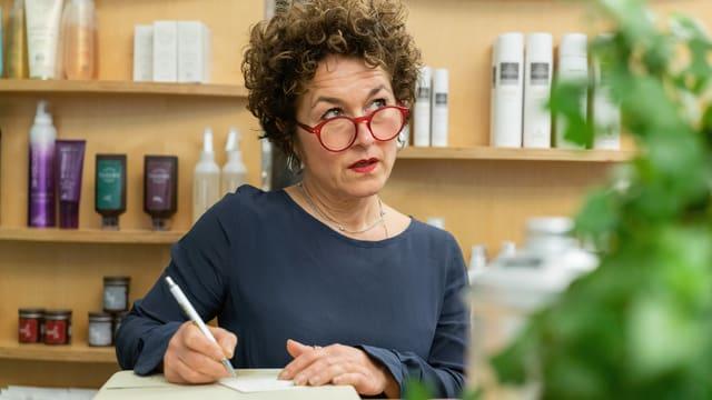 eine Frau mit Brille trägt Notizen in ein Buch ein