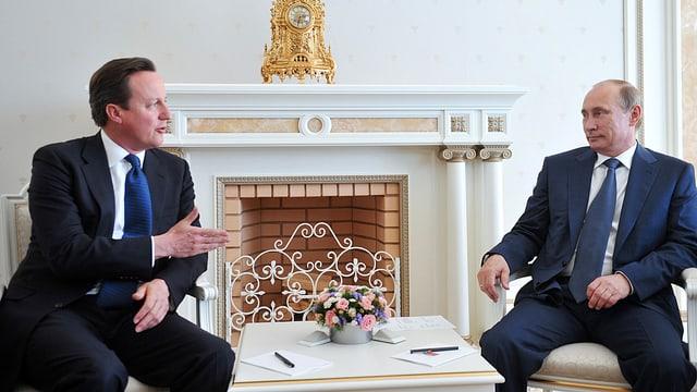 Cameron und Putin reden miteinander. Zwischen ihnen ist ein Tischchen.
