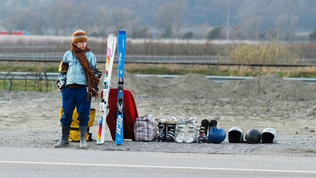 Ein Junge steht neben einem Haufen Skiausrüstung am Strassenrand.