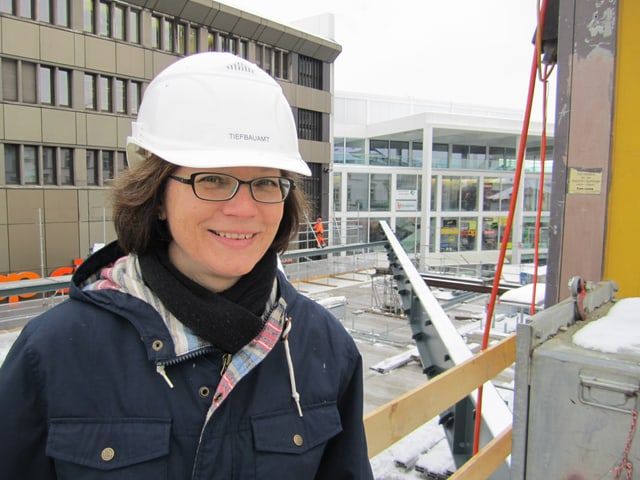 Stadträtin Pearl Pedergnana mit blauer Jacke und weissem Baustellenhelm vor einem Stahlträger.