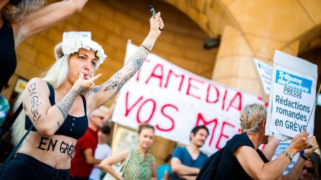 Frau pfeift mit dem Mund, im Hintergrund Menschen mit Transparenten