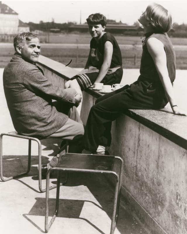 Ein Mann und zwei Frauen sitzen auf einer Mauer.