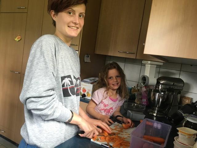 Mutter schält Karotten mit Kind.