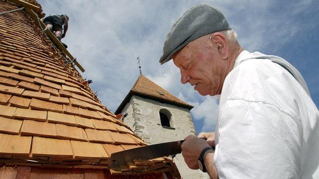 Alter Mann arbeitet an einem Kirchendach
