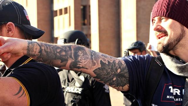Ein junger Mann streckt seinen tätowierten Arm aus.