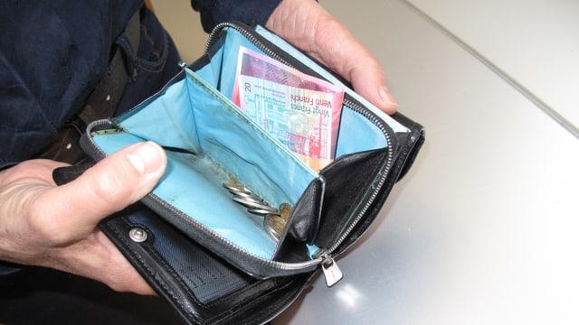 Blick in ein Portemonnaie mit einer 20er-Note und etwas Münz.
