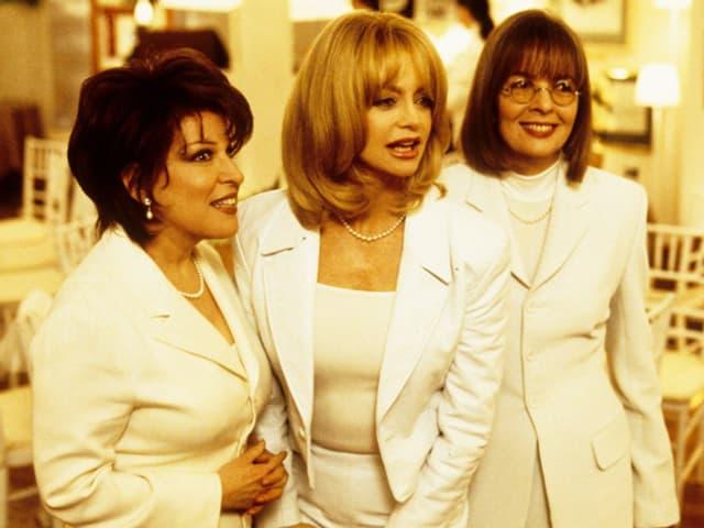 Drei Frauen in weissen Anzügen.