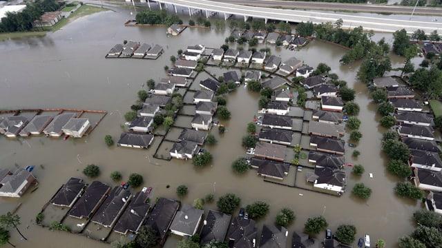 Inundaziuns a Houston, in abitadi da chasas d'ina familia sut aua.