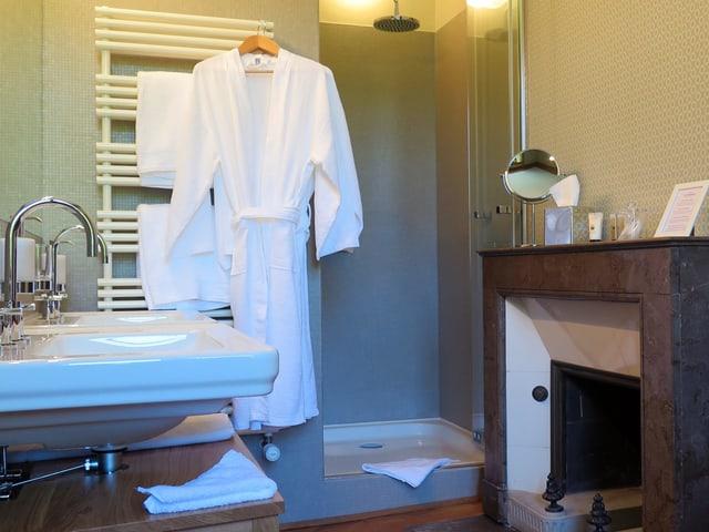 Kamin und moderne Dusche: Blick in ein Badezimmer.