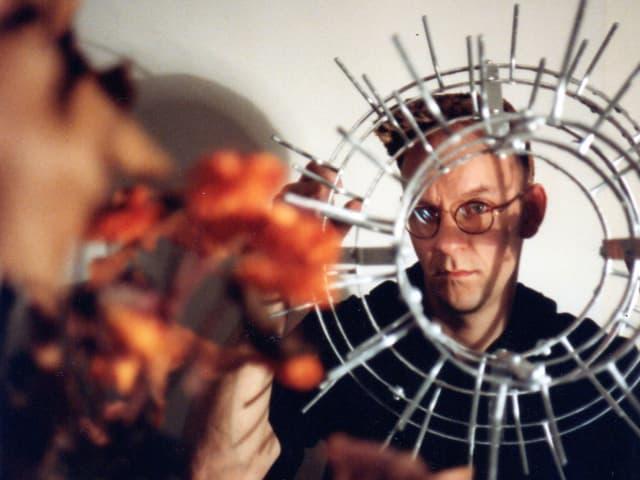 Ein Amnn mit Brille schaut durch ein rundes Objekt aus Metall in die Kamera.