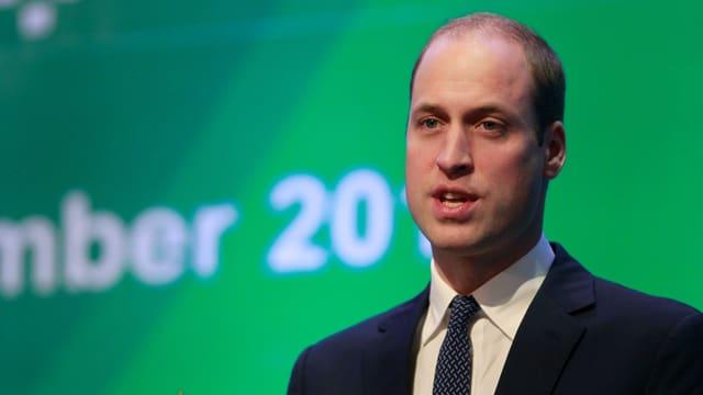 Prinz William im Anzug vor einem grünen Hintergrund.