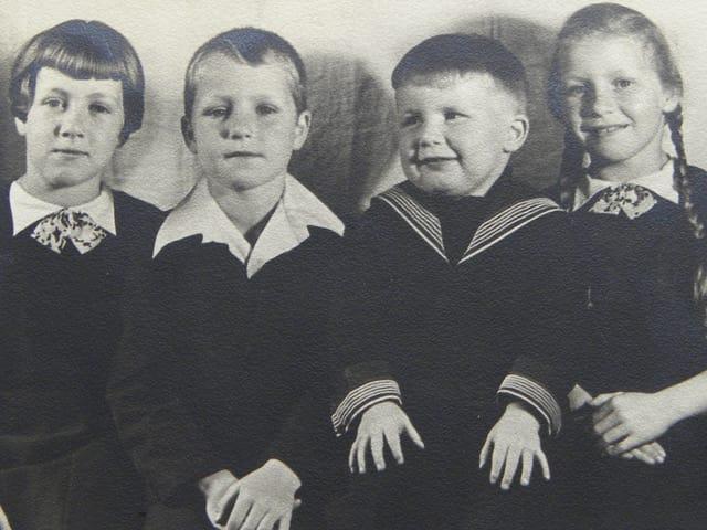 Schwarz-Weiss Fotografie mit vier Kindern, die in einer Reihe sitzen.