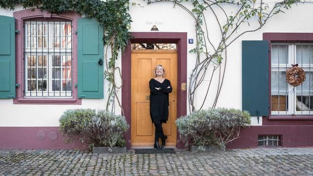 Eine Frau steht vor einem mit Pflanzen bewachsenen Wohnhaus.