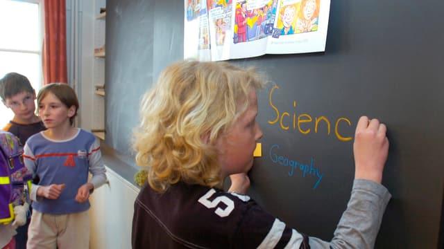 Ein Kind an der Wandtafel beim Frühenglisch.