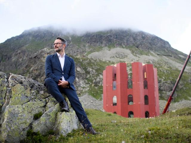 Berglandschaft mit rotem Turm, davor sitzt Giovanni Netzer auf einem Stein
