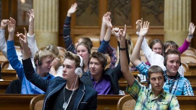 Schüler sitzen mit erhobener Hand im Saal des Nationalrates im Bundeshaus in Bern.