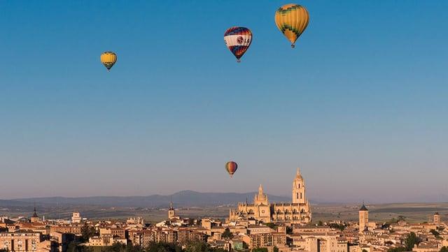 Eine Stadt mit vielen alten Gebäuden. èber der Stadt schweben vier Heissluftballone.