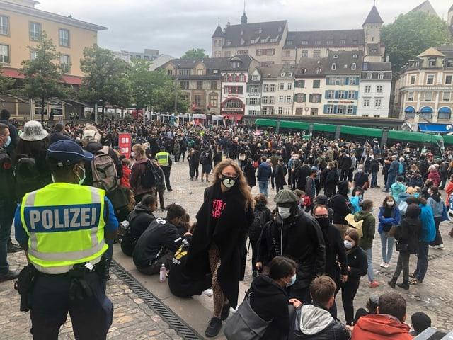 Demo-Teilnehmende und ein Polizist