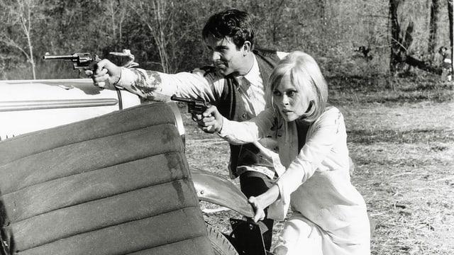 Eine Frau und eine Mann stehen hinter einem Auto. Beide haben eine Waffen in der Hand und schiessen in die selbe Richtung.
