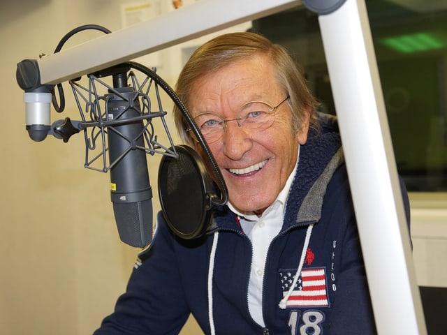 Ein lachender Mann mit Brille vor einem Mikrofon.